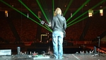 Laser beams shine as Martin looks out over an empty arena